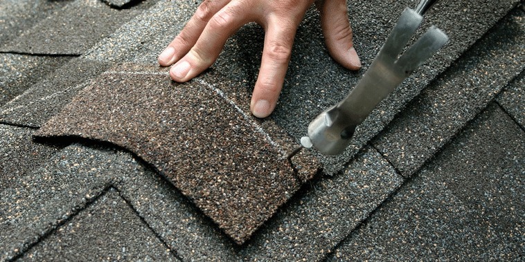 hammering a nail into a shingle