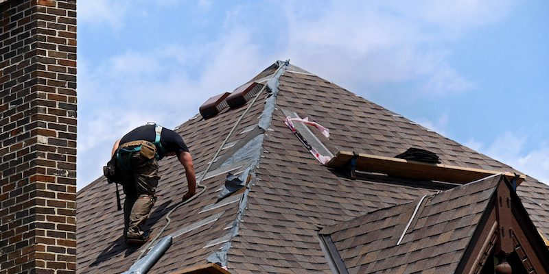 roofer on the roof fixing shingles