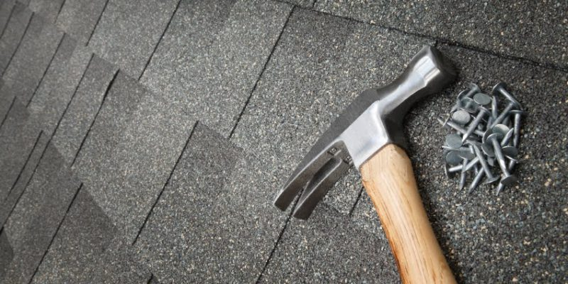 a hammer on a roof with loose nails