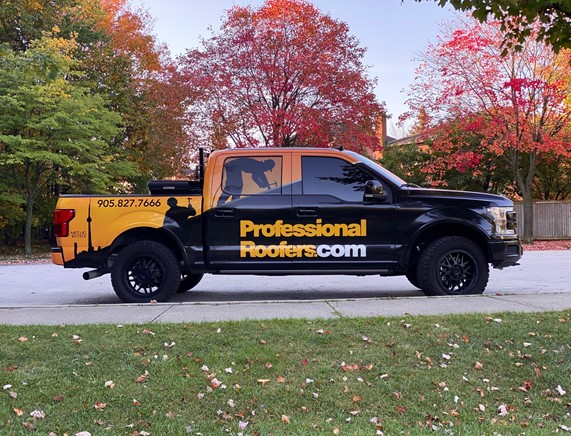 Picture of Professional Roofers' pickup truck wrapped with branding elements, website, and phone number